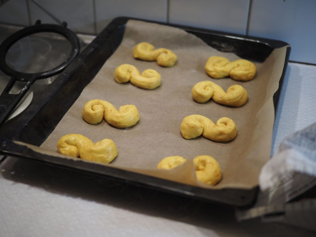 Tray of saffron buns arranged on a tray before rising a second time and being baked.